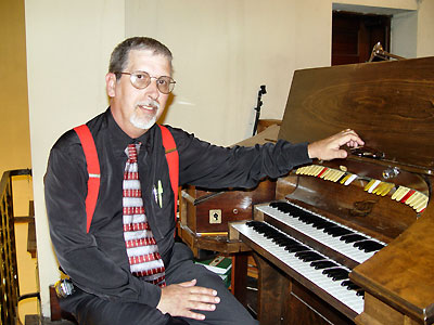 Click here to see more pictures of the fine little organ you see Tom Hoehn seated at.